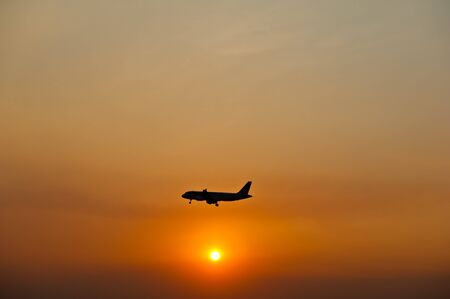 aircraft landing: Airplane silhouette over sunset Stock Photo