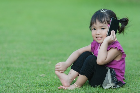 Little baby girl with mobile phone on grass Stock Photo - 13407991