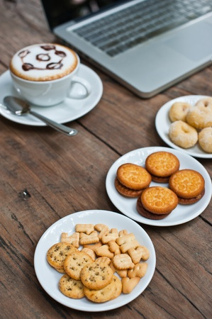 Laptop with coffee cup and snack on wood table photo