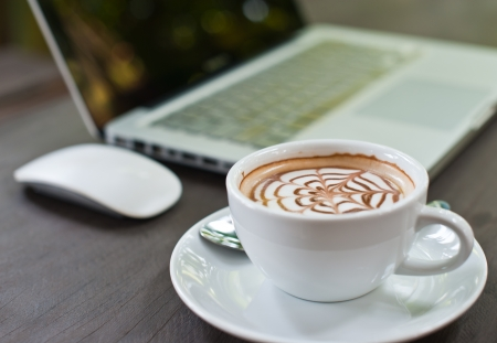 Laptop with coffee cup on wood table photo