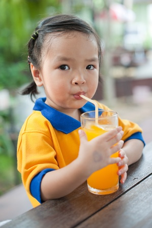 Little girl drinking orange juice Stock Photo - 13592146