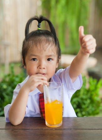 Little girl drinking orange juice photo