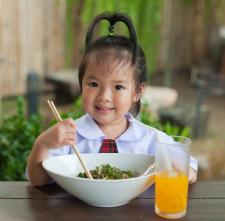 Little girl eating noodle and orange juice photo