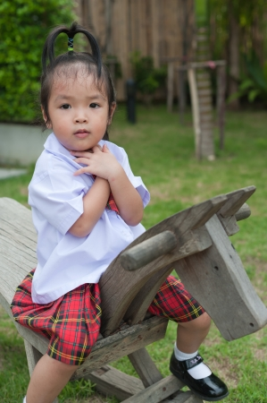 Little girl riding on wooden horse photo