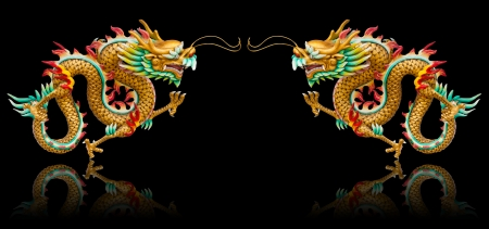 Twin golden dragon statues on black background with reflection