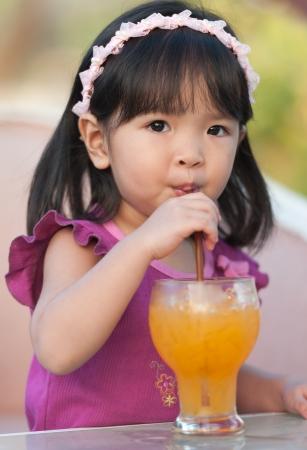 chinese drinks: Little girl drinking orange juice