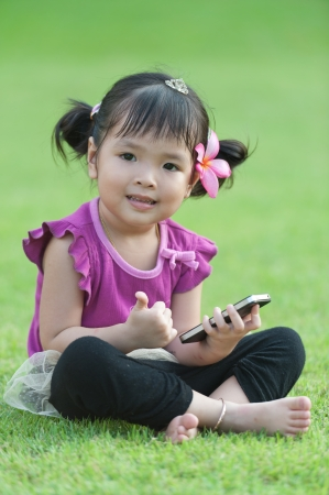 Little baby girl with mobile phone on grass photo