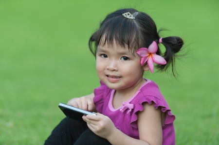 Little baby girl with mobile phone on grass Stock Photo - 14109570