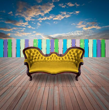 Golden armchair on wood floor with fence and sky photo