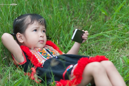 Little girl laying on grass with mobile phone photo