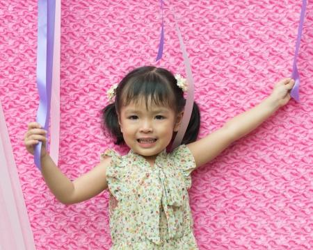 Portrait of little Asian girl on pink Stock Photo - 15796764