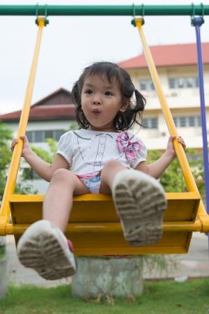 columpios: niña le gusta jugar en un parque infantil