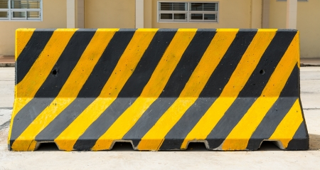 Yellow and black concrete barriers blocking on the road