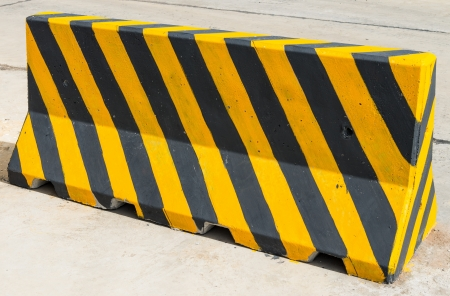 Yellow and black concrete barriers blocking on the road photo