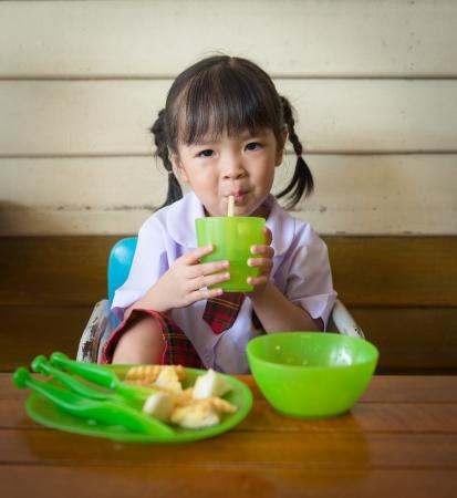 little girl have lunch at restaurant Imagens