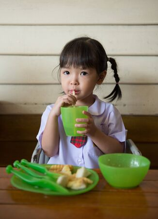 little girl have lunch at restaurant photo
