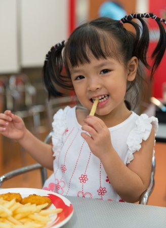 Little girl eating french fries at fast food restaurant Banque d'images