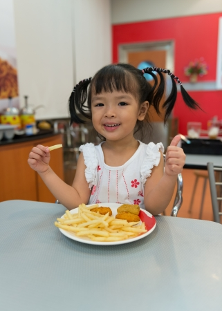 Little girl eating french fries at fast food restaurant photo