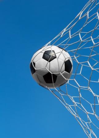 soccer ball in net on blue sky Standard-Bild