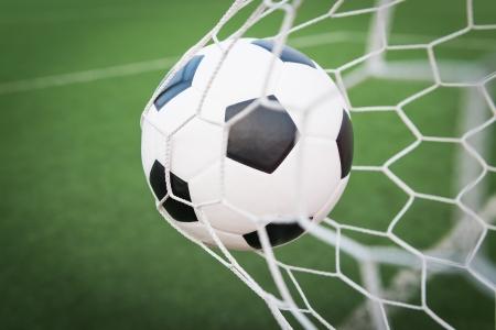 pelota de futbol: bal�n de f�tbol en la red de la porter�a con la hierba verde
