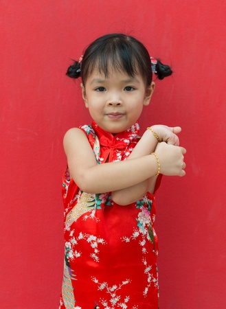 little chinese girl with smart phone on red wall Stock Photo - 21231119