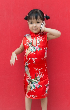 little chinese girl with smart phone on red wall Stock Photo - 21231120