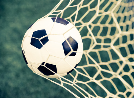 soccer ball in goal net with green grass - retro vintage filter effect