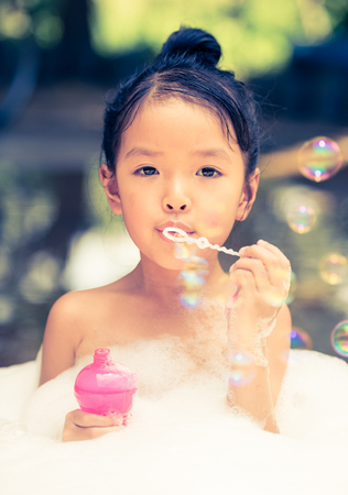 asian girl playing with water and foam - retro vintage filter effect