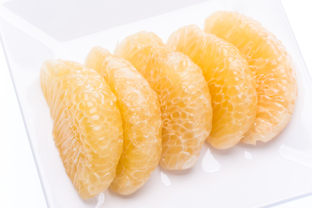 slice pomelo on dish on white background