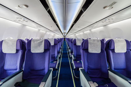 Asientos de avión de pasajeros vacíos en la cabina