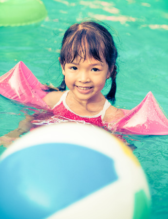 Little girl swimming in pool, retro vintage filter effect