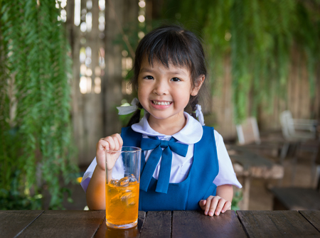 Little school girl drinking orange juice