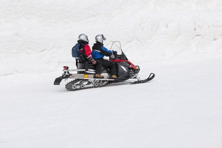 Couple driving snowmobile in snowy field