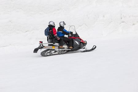 snowy field: Couple driving snowmobile in snowy field