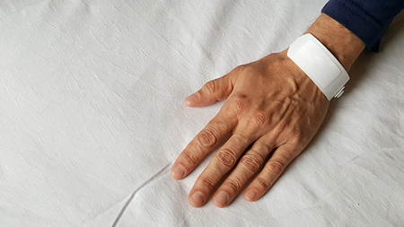 Hand of man with identification wrist bands in hospital bed Stock Photo - 71880246