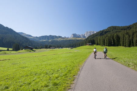 Mountain bikers on trail, National park, Alpe di Siusi, Dolomites, Italy Stock Photo