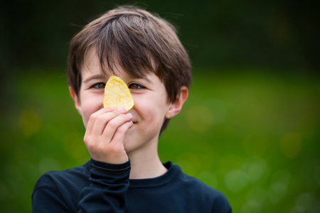 Kid holding one crisp behind His Eyes