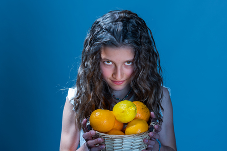 Portrait of young girl holding basket with fruits