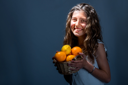 Beautiful smiling girl-teenager holding basket with oranges and lemons, on blue background Stock Photo - 77501596