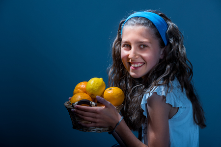 Attractive young girl with basket of citrus on dark background Stock Photo
