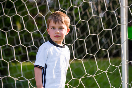 Active cute little kid playing European football outdoors on field