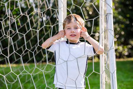 Boy playing football, looking through net