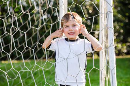 Cute little boy playing football, looking through net