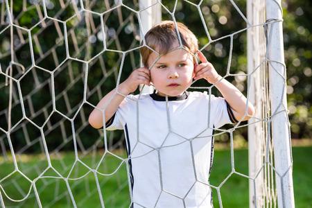 Child looking through European football net on football field