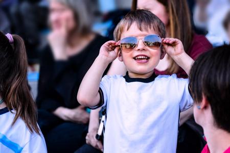 Smiling child wearing sunglasses standing in the stadium