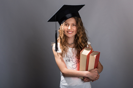 Young college graduate girl holding books