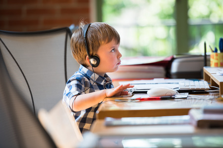 One cute baby wearing headphones, looking at computer screen Stock Photo