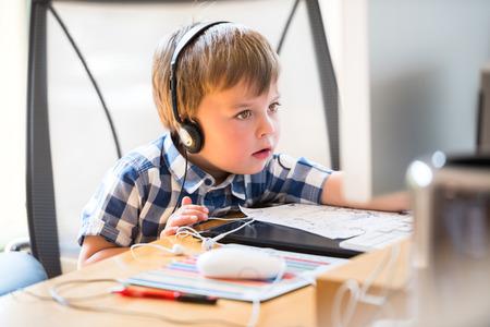 Kid wearing headphones while using computer