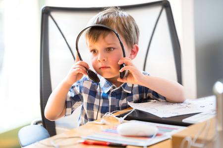 Child sit in office wearing headphones