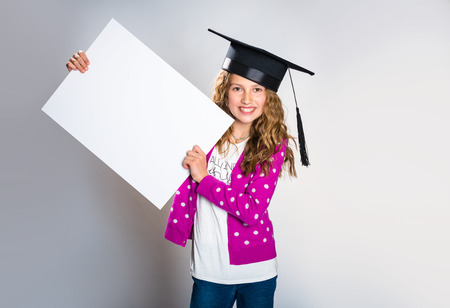 Happy teenager holding white board looking at camera